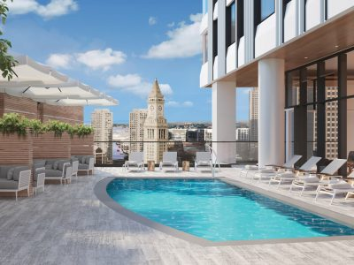 Pool deck with view to Custom House. Deck chairs in front of indoor amenity space. Lounge seating with umbrellas to left.