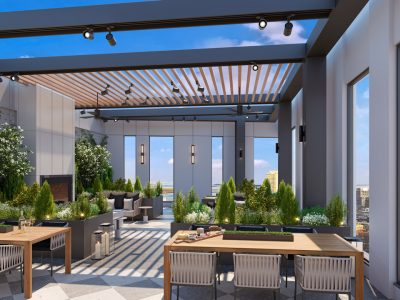 Two wood dining tables & and green shrubs dominate image of Sudbury Sky Terrace. Lounge with fireplace & trees beyond.